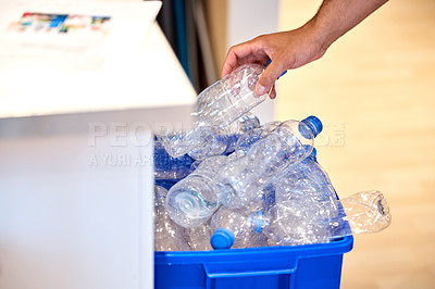 Buy stock photo Cropped shot of a man putting a bottle in the recycling bin at home