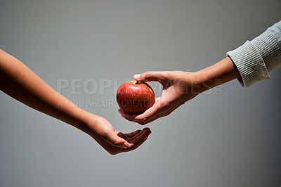 Buy stock photo Studio shot of a unrecognizable woman offering a child an apple