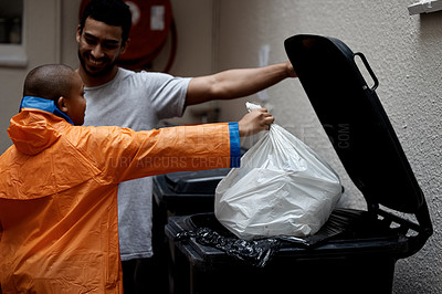 Buy stock photo Shot of a father and son putting newspaper in the bin to be recycled