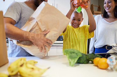 Buy stock photo Shot of a family unpacking the groceries in the kitchen at home
