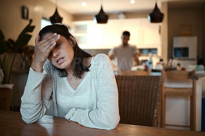 Buy stock photo Shot of a woman looking stressed while sitting at home with her boyfriend standing in the background