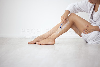 Buy stock photo Cropped shot of an unrecognizable woman sitting down and shaving her legs at home