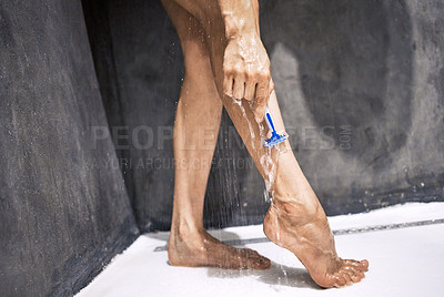 Buy stock photo Cropped shot of an unrecognizable woman standing in the shower at home and shaving her legs
