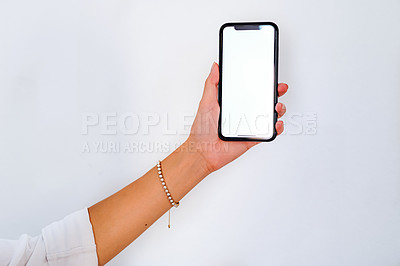 Buy stock photo Cropped shot of an unrecognizable businesswoman standing alone against a white wall and holding her cellphone