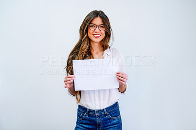 Buy stock photo Shot of an attractive young businesswoman standing alone against a white wall and holding a blank placard