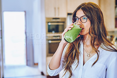 Buy stock photo Shot of a young woman having a healthy smoothie at home