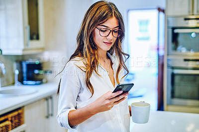 Buy stock photo Shot of a young woman having coffee and using a smartphone at home