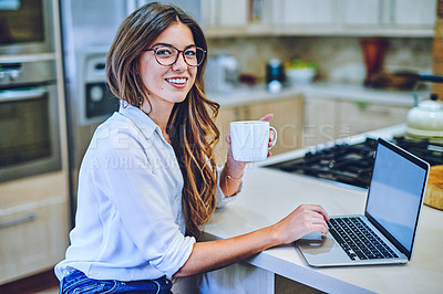 Buy stock photo Shot of a young woman having coffee and using a laptop at home
