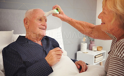 Buy stock photo Shot of an elderly woman taking her husbands temperature in bed at home