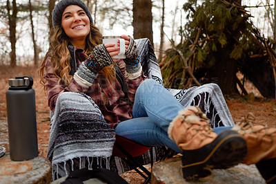 Buy stock photo Shot of a young woman drinking a warm beverage while camping in the wilderness during winter