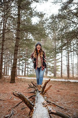 Buy stock photo Shot of a young woman walking on a tree log in the wilderness during winter