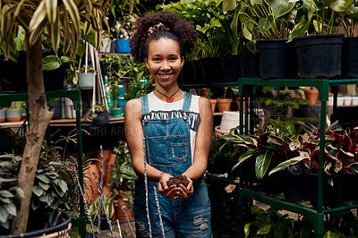Buy stock photo Portrait of a young woman holding soil while working in a garden centre