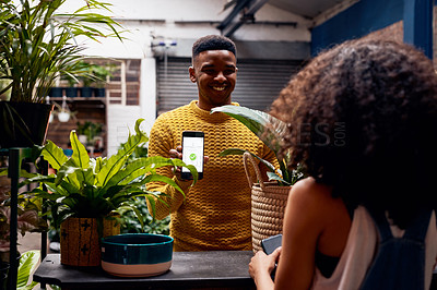 Buy stock photo Shot of a young man using a smartphone to pay for plants at a garden centre