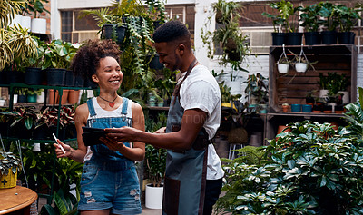 Buy stock photo Shot of a young man and woman using a digital tablet while working in a garden centre