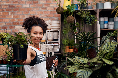Buy stock photo Shot of a young woman using a digital tablet while working in a garden centre