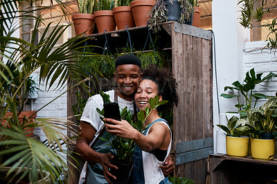 Buy stock photo Shot of a young man and woman taking selfies while working in a garden centre