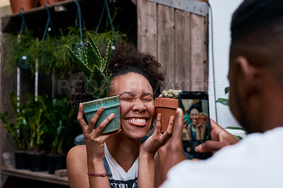 Buy stock photo Shot of a young man and woman taking pictures of a plant while working in a garden centre