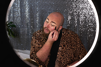 Buy stock photo Shot of a young man applying theatrical makeup to his face in a studio