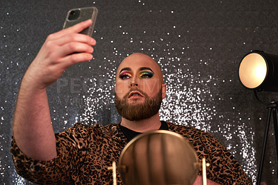 Buy stock photo Shot of a young man using a smartphone to take selfies after applying theatrical makeup in a studio