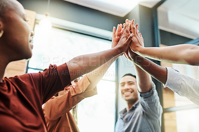 Buy stock photo Low angle shot of a group of businesspeople giving each other a high five in an office