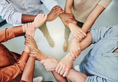 Buy stock photo High angle shot of a group of businesspeople holding one another's wrists in a circular formation