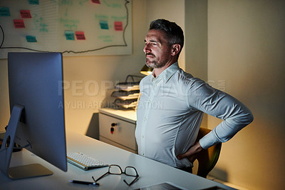 Buy stock photo Shot of a mature businessman experiencing back pain while working on a computer in an office at night