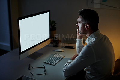 Buy stock photo Shot of a mature businessman working on a computer in an office at night