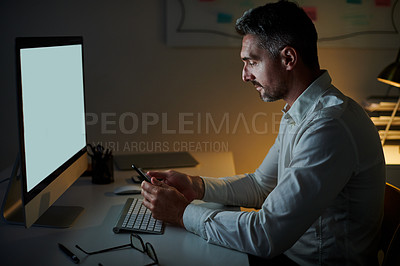 Buy stock photo Shot of a mature businessman using a cellphone while working on a computer in an office at night