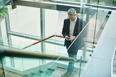 Buy stock photo Shot of a mature businessman using a cellphone while standing on a staircase in an office