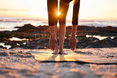Buy stock photo Cropped shot of an unrecognizable woman doing yoga alone on the beach at sunset