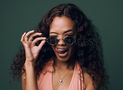 Buy stock photo Cropped portrait of an attractive and quirky young woman posing against a green background in studio