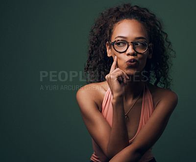 Buy stock photo Cropped shot of an attractive and quirky young woman posing against a green background in studio