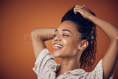 Buy stock photo Shot of a young woman with wet hair posing against an orange background