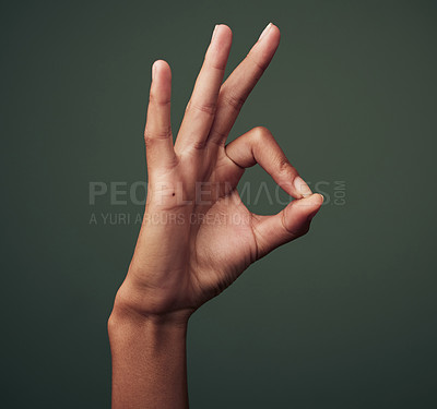 Buy stock photo Studio shot of an unrecognisable woman making an okay gesture against a green background