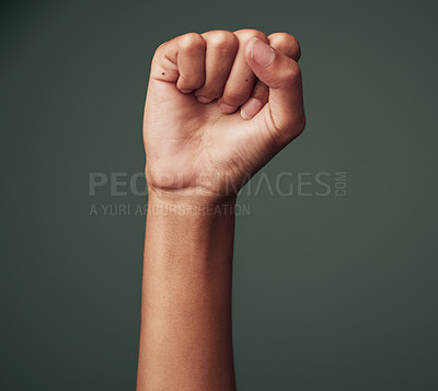Buy stock photo Studio shot of an unrecognisable woman raising her hand in strength against a green background