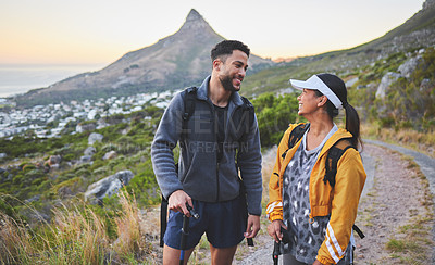 Buy stock photo Shot of a young couple hiking at sunset on a mountain range outdoors