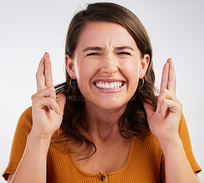 Buy stock photo Studio shot of a young woman crossing her fingers in hope  against a white background
