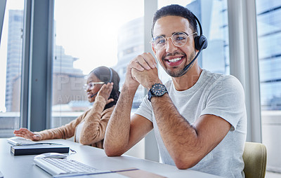 Buy stock photo Shot of male and female colleagues working together in their office at a call center