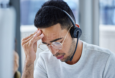 Buy stock photo Shot of a young businessman suffering s headache at his desk in his office