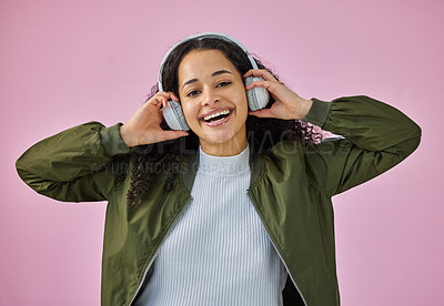 Buy stock photo Shot of an attractive young woman standing against a pink background in the studio and listening to music through headphones