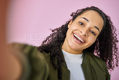 Buy stock photo Shot of an attractive young woman standing alone against a pink background in the studio and taking a selfie