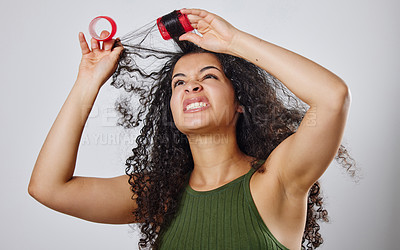 Buy stock photo Shot of a woman frowning while pulling rollers out of her hair