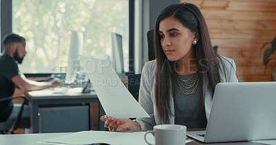 Buy stock photo Shot of a young businesswoman sitting at her desk reading some documents in her office