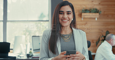 Buy stock photo Shot of a young businesswoman standing using her smartphone in her office
