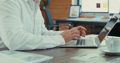 Buy stock photo Shot of an anonymous businessman sitting at his desk using his laptop
