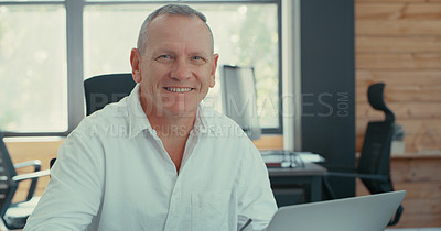 Buy stock photo Shot of an older businessman sitting in office using his laptop