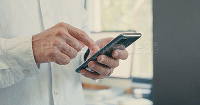 Buy stock photo Shot of an unrecognizable businessman using his smartphone in his office