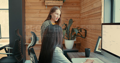Buy stock photo Shot of two young businesswomen having a meeting in their office