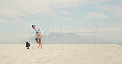 Buy stock photo Shot of a man spending the day at the beach with his dog