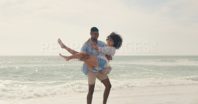 Buy stock photo Shot of a man carrying his girlfriend while spending the day at the beach